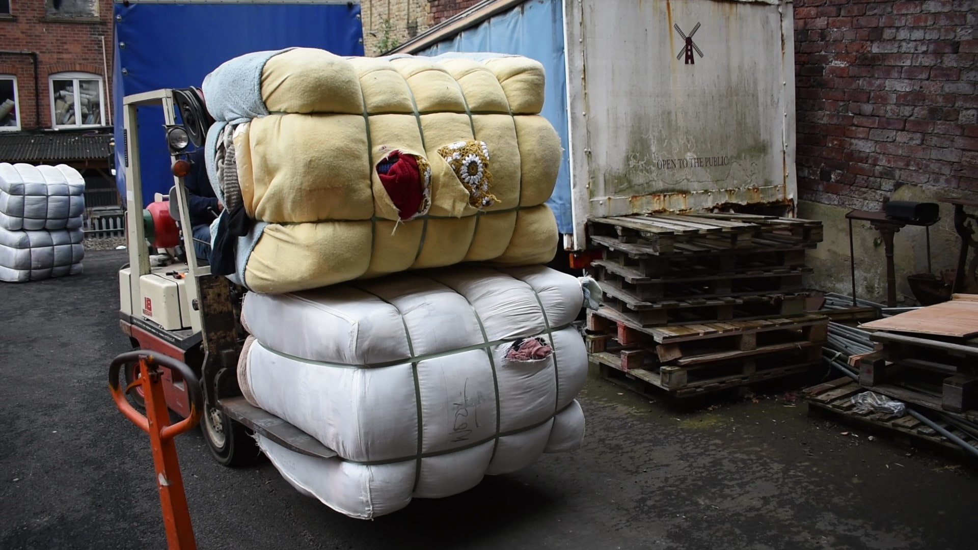 unloading bales of wool clothing for recycling