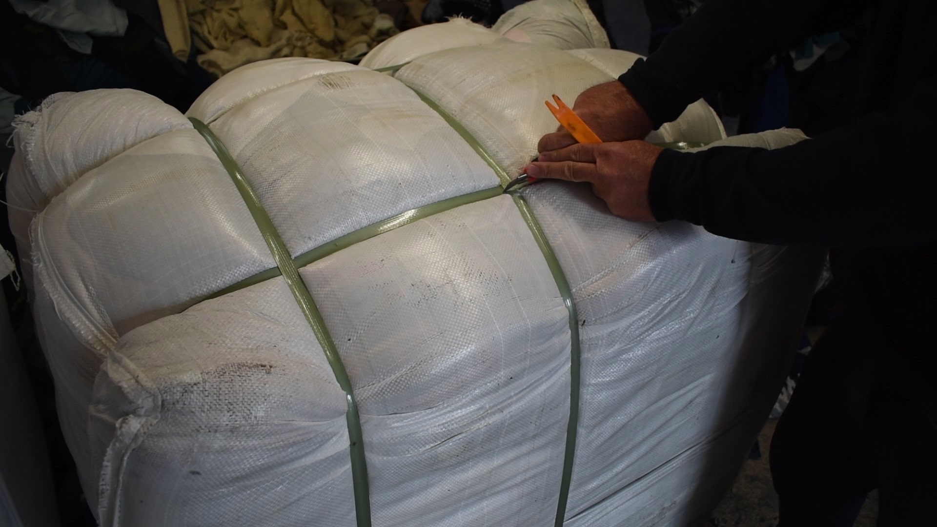 opening a bale of used wool clothing